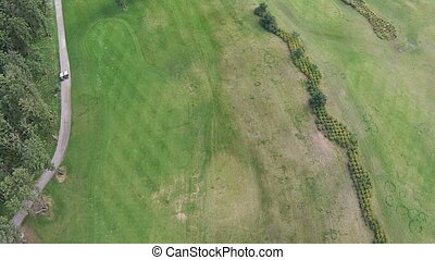 A drone flies over a green golf course