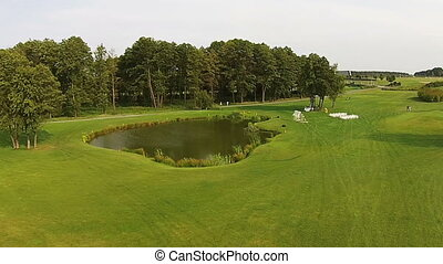 A drone flies over a green golf course. Wedding preparations