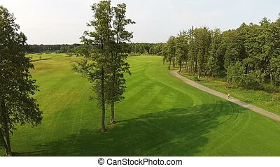 A drone flies over a green golf course with lake