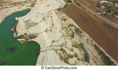 A drone flies over a quarry, a lake and a field - The drone...
