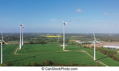 a drone flight over fields in spring and windmills