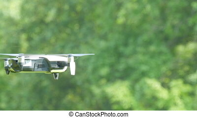 A drone or quadrocopter of white color flies in the air against the background of a green forest. Future technologies