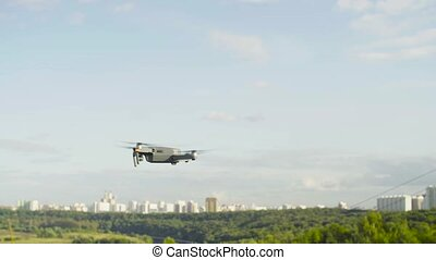 A drone quadrocopter with camera flying in the sky