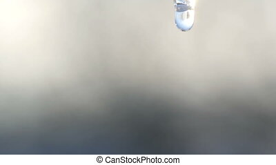 A drop of pure water dripping from the top of a melting...