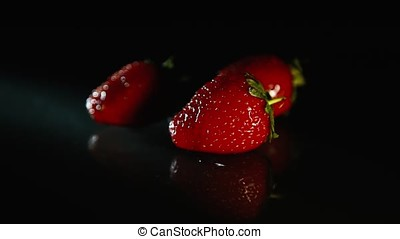A drop of water falls on the strawberry