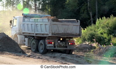 A dump white truck ready to unload and running backwards