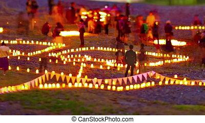 A dusk timelapse of burning romantic candles medium shot tiltshift zoom