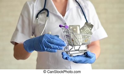 A faceless female pharmacist holds a mini shopping cart with medications and gestures with the ok. Taking vitamins is the key to good health. Doctor's recommendations