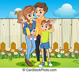 A family at the backyard with a wooden fence