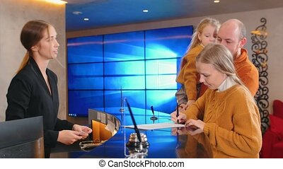 A family checking in the hotel - a woman singing the papers ...