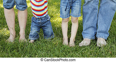 Family feet in jeans on the grass