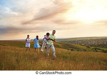 A family is having fun walking in the sunset