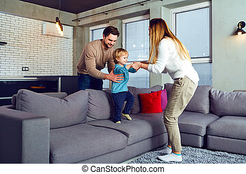 A family is playing with a child in the room.