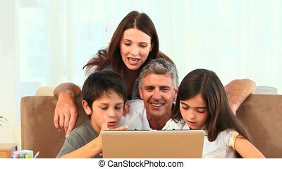 A family looking at a laptop on a table