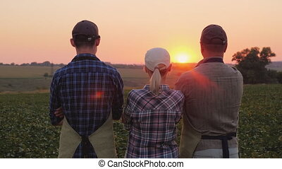 A family of farmers after work day admire the sunset over...