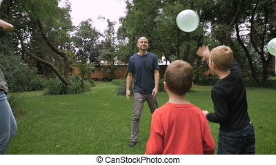A family of five have a day in the park together playing with balloons - slowmo