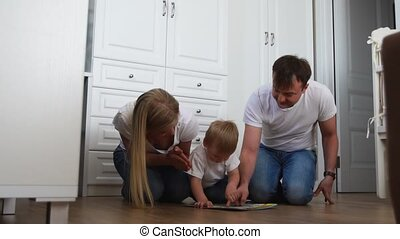 A family of three in white T-shirts and blue jeans sitting on the floor of their bedroom playing with the boy in intellectual games. Slow-motion shooting happy family