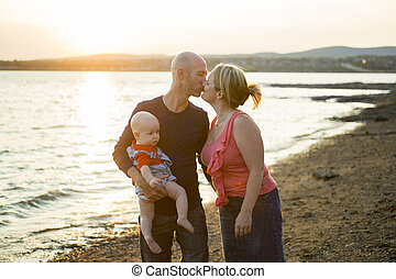 Family of three person is standing on sunset and sea backdrop