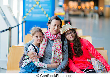 A family of three sitting in a recreation area at the airport