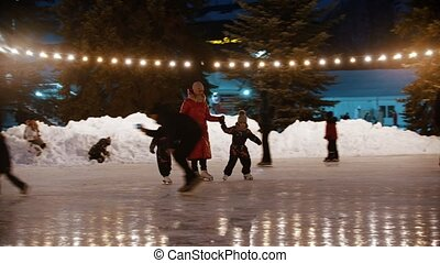 A family of young mother and two kids skating on the decorated ice rink holding their hands