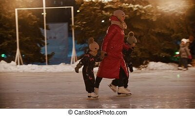 A family of young mother and two kids skating on the ice rink holding their hands