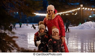 A family of young mother and two kids standing on the decorated ice rink and waving with their hands