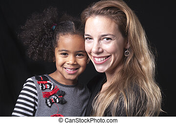 family posing on a black background studio