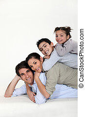 a family pyramid - Family laying on each other's backs