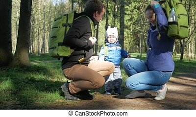 A family with a beautiful baby is going on a hike in the forest. They put on backpacks and follow the path. The sun is breaking through the leaves