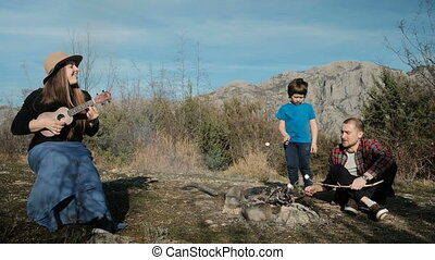 A family with a child rests on a picnic by the fire and sings songs.