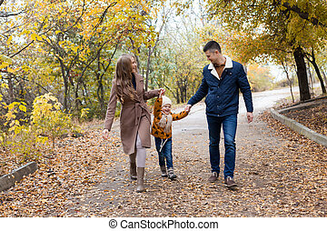 a family with a young son walk in the Park in autumn