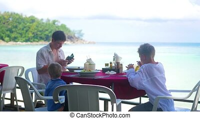 A family with children dines at a restaurant on the beach....