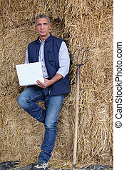 a farmer with a computer leaning against straw bales
