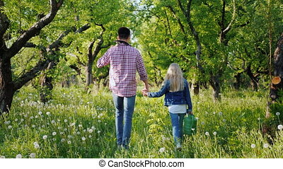 A farmer with a younger sister walks through the apple...