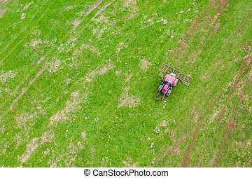 a farming machine from above on a green meadow