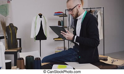 A fashion designer sits on the table in the atelier and draws sketches for tailoring the new collection of clothes. A bearded tailor wearing glasses, dressed in a white shirt and a black blouse with a measuring tape on his neck, working in the atelier