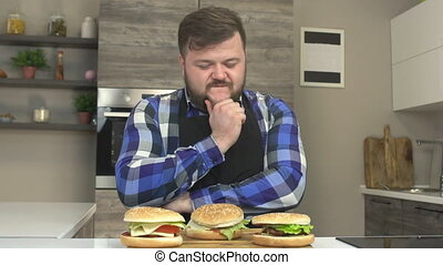A fat caucasian man with a beard is sitting in the kitchen...