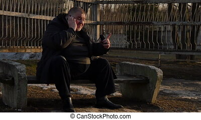 A fat man talking on the phone and very nervous on city street.