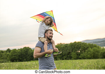 father and child on meadow with a kite in the summer