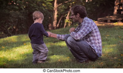 A father and cute toddler son spending time together outside in nature in slomo