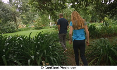 A father and daughter walking through a park together-...