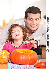 a father and his little girl laughing and eating a pumpkin