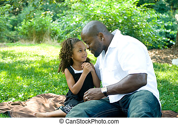 A father and his mixed race daughter enjoying the park