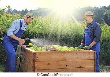 Father and son gardening on a raised planting bed in a garden