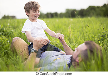 Father and son having fun outdoors in the meadow