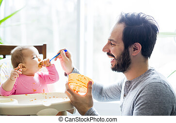 father feeding his little baby daughter