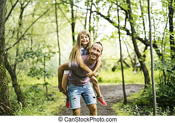 Father giving his daughter a piggyback ride, having fun