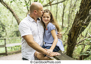 Father having fun in forest with his daughter