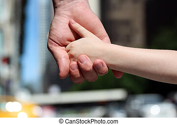 a father holds the hand of a small child outdoor