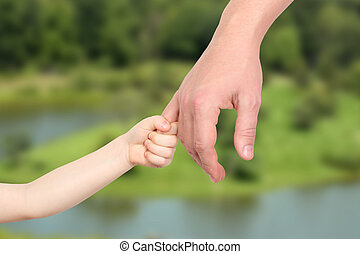 a father  holds the hand of a small
